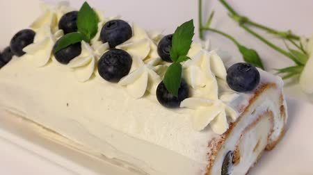 покрытый : Sponge cake coated with cream and garnished with dried blueberries and fresh mint leaves. Nearby a white rose. Close-up shot Стоковые видеозаписи