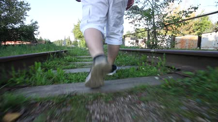 sleepers : A young man walks on the sleepers of an old railway. His legs are visible. Stock Footage