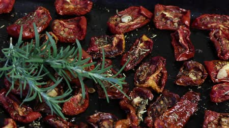 mentiras : Sun-dried tomatoes with spices and garlic on a baking sheet. On top of them lies fresh rosemary.