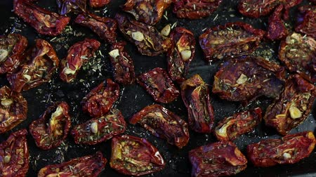 готовые к употреблению : Sun-dried tomatoes with spices and garlic on a baking sheet. On top of them lies fresh rosemary. Vertical movement. Стоковые видеозаписи