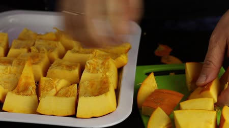 A man cuts an orange pumpkin into pieces. Pieces stacks on a tray. World Vegan Day.