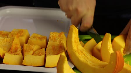 tykev : A man cuts an orange pumpkin into pieces. Pieces stacks on a tray. World Vegan Day.