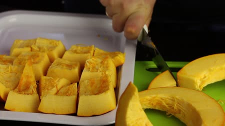 kalebas : A man cuts an orange pumpkin into pieces. Pieces stacks on a tray. World Vegan Day.