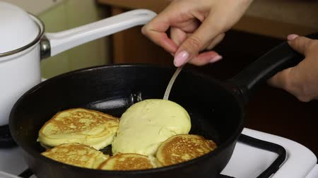 A woman is frying pancakes. Flips with a fork. Stockvideo
