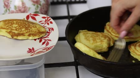 A woman is frying pancakes. Shifts the finished pancakes from the pan to the plate.