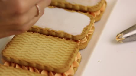 A woman is preparing pastries from cookies and cream. Drizzles cookies with milk to soften. Stockvideo