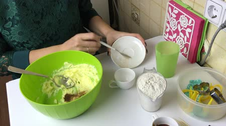 A woman mixes gingerbread cookie ingredients in a container. Adds flour and kneads cookie dough.