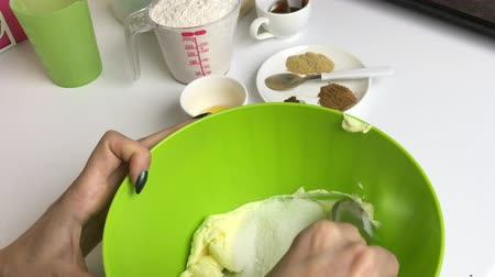 A woman mixes gingerbread cookie ingredients in a container.