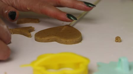 Woman is preparing gingerbread cookie. She inserts a stick into the cookie blank. Close-up shot.