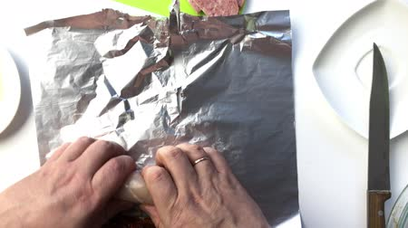 A man wraps a roll. From chicken, lard, cheese, salami and sun-dried tomatoes. View from above. Dostupné videozáznamy