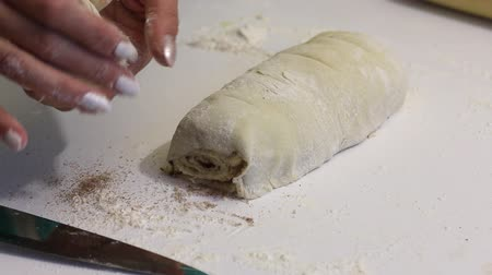 tekercselt : A woman cuts with a knife rolled into a roll dough for cinnabons. Nearby are cooking tools.