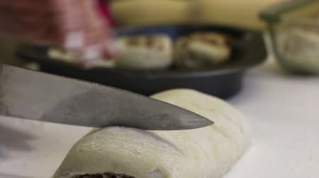 A woman cuts pieces from a roll of rolled dough for cinnabons. Lay them on a baking sheet.