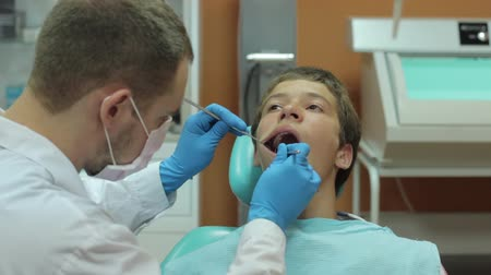 male : Dentist carry out routine inspection of the mouth of a boy video close-up
