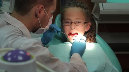 dişçi : Dentist carry out routine inspection of the mouth of a little girl close-up video