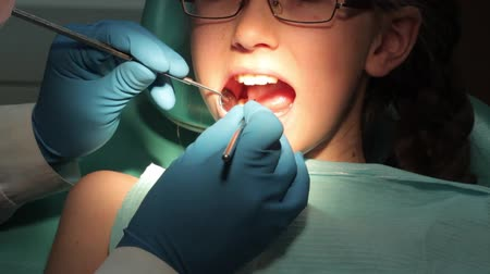trabalhar fora : Dentist carry out routine inspection of the mouth of a little girl close-up video