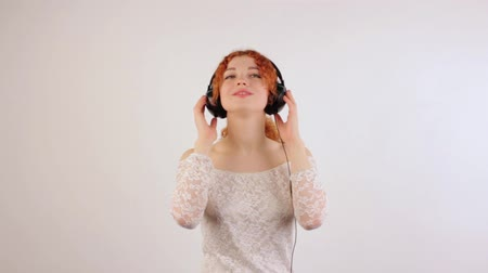 vöröshajú : Young girl with red curly hair with headphones on her head dancing to music