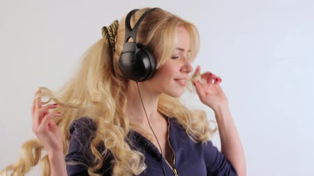 наушники : Young blonde girl with headphones on her head dancing while listening to music, in the end makes a kiss at the camera Стоковые видеозаписи