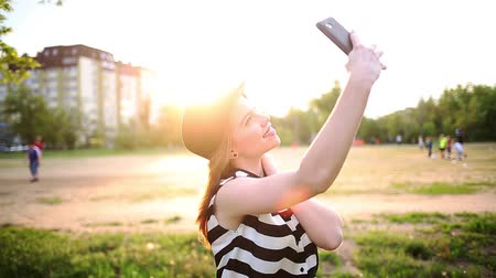 telefone celular : Young attractive girl in the hat does cheerful selfie on a cellphone. The concept of urban street youth fashion. Communication in social networks. Stock Footage