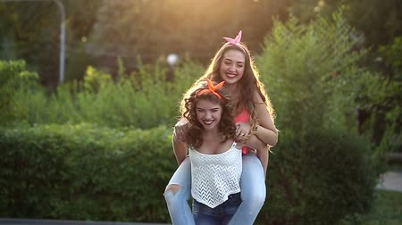 детеныш : Cheerful girlfriend meet in park. Girl holds the girlfriend on piggyback. The concept of true friendship.