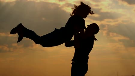 társkereső : Silhouette of couple in love outdoors. The girl ran to her boyfriend. The man takes the girl in his arms and throws up. A passionate kiss. Stock mozgókép