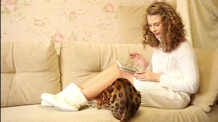 elkényeztet : Young girl playing on a tablet computer. Bengal cat playing with a shoe girl. Pet. Social networks and animals.
