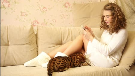 breeder : Young girl playing on a tablet computer. Bengal cat sitting next to the hostess. Pet. Social networks and animals.