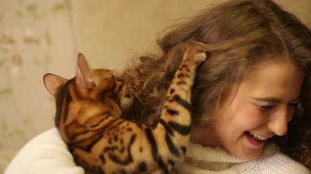 elkényeztet : Bengal cat bites his mistress. Lovely girl and pet. Games with animals. Home comfort. Friends. Stock mozgókép