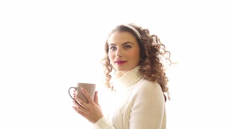 pulóver : Young cute girl drinking hot tea at the window. Girl with curly hair. Girl in warm white sweater. Home comfort.