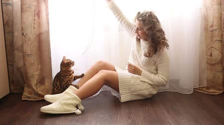 elkényeztet : Young cute girl playing with bengal cat sitting on the floor near the window. Girl with curly hair. Girl in warm white sweater. Home comfort.