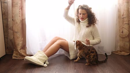 elkényeztet : Young cute girl playing with bengal cat sitting on the floor near the window. White pearl necklace. Girl with curly hair. Girl in warm white sweater. Home comfort.
