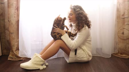 elkényeztet : Young cute girl playing with bengal cat sitting on the floor near the window. Girl with curly hair. Girl in warm white sweater. Home comfort. Pet.