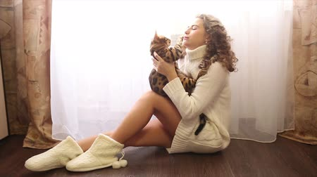 elkényeztet : Young cute girl hugging bengal cat sitting on the floor near the window. Girl with curly hair. Girl in warm white sweater. Home comfort. Pet. Stock mozgókép