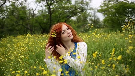 kudrnatý : Cute red-haired girl straightens curly hair. Girl sits on a meadow among the wildflowers. Female face close up. Slow motion Dostupné videozáznamy