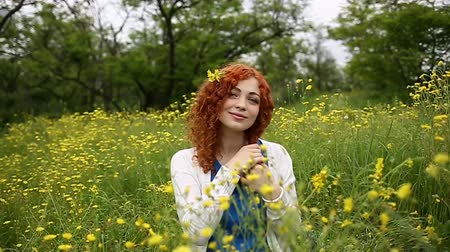 kıvırcık : Cute red-haired girl straightens curly hair. Girl sits on a meadow among the wildflowers. Female face close up. Slow motion Stok Video