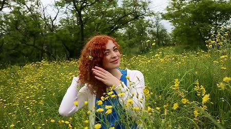 kıvırcık : Cute red-haired girl straightens curly hair. Female face close up. Slow motion