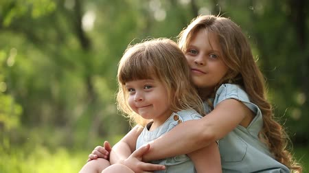 сестра : Two sisters. The older girl hugging and kissing the younger. Family time.