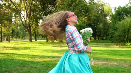 brown dress : Young attractive woman with a bouquet of wildflowers whirl. She is dressed in a skirt, a plaid shirt and glasses. Slow motion. Unbridled joy. Long hair flying