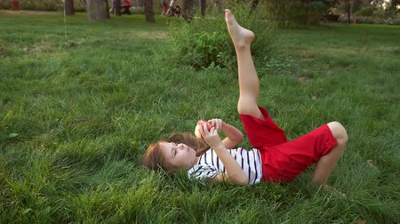 sadece kadınlar : Little girl is eating an apple lying on the green grass in the park. Have a bite in the open air. Barefoot Stok Video