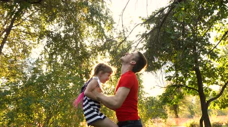 lánya : The father throws the little daughter up. She is laughing. Family vacation in the park. Joy of paternity.