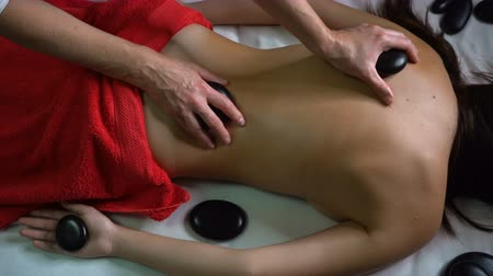 kamień : Spa treatments. Back massage with hot stones. The girl relaxes. Healing procedures. Exotic massage. Heating massage