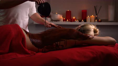revitalizing : Spa treatments. Back massage with moisturizing mask. Process of applying a mask. Deep moisturizing and regenerative procedures. Body scrub with chocolate