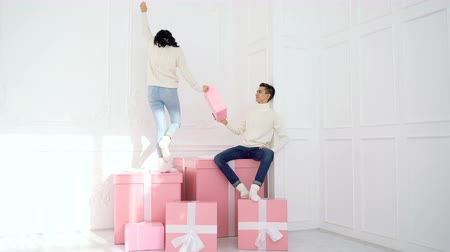 nişanlısı : Loving couple of teenagers and Christmas presents. Nice girl is standing on a big box in white sweater. Boyfriend gives a gift, and she drops it on floor Stok Video