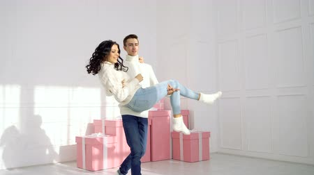 fiancee : Loving couple of teenagers and Christmas presents. Boyfriend is holding his girlfriend in arms and circling. They are dressed in white sweaters and jeans.