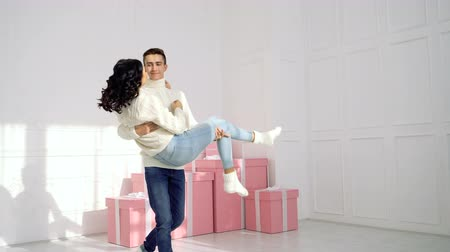 fiancee : Loving couple teenagers and Christmas gifts. Boyfriend is holding his girlfriend in arms and circling her. They are dressed in white sweaters and jeans.