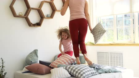 Family time. Mother and daughter jump on the bed and fight with pillows in the bedroom early in the morning. Happy childhood.