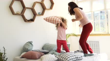 Family time. Mother and little daughter jump on the bed and fight with pillows in the bedroom early in the morning. They fall on the bed and embrace. Happy childhood.