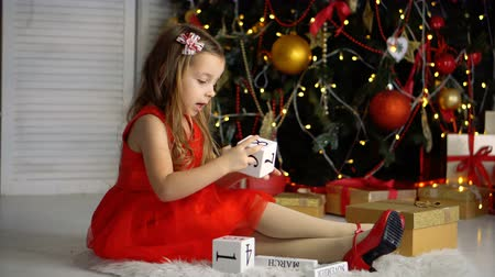 Cute little girl in red dress and shoes sitting next to the Christmas tree and playing with blocks. Happy childhood.
