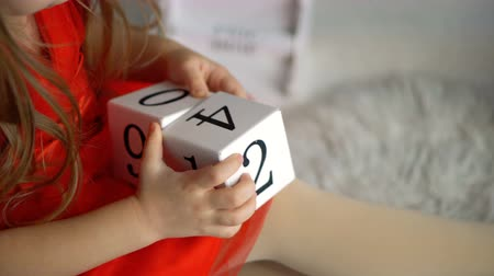 Little girl is playing with blocks with numbers. Shooting close-up of hands and toys. Happy childhood. Educational games.