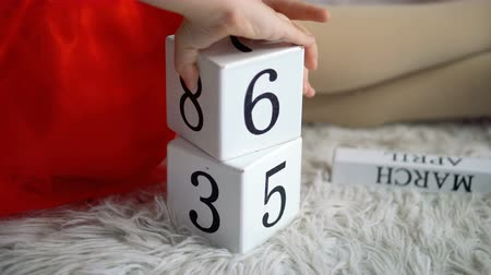 Little girl is playing with blocks with numbers. She builds tower. Shooting close-up of hands and toys. Happy childhood. Educational games.
