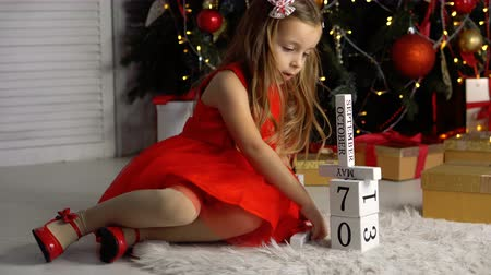 Nice little girl in a red dress. She builds a tower. In the background is a tree with garlands and gifts. Dostupné videozáznamy
